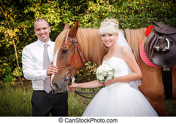 groom and the bride during walk in their wedding day against a brown horse