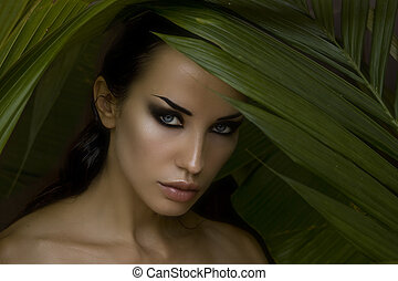 Sexy beautiful woman hiding behind the palm leaves Beautiful...