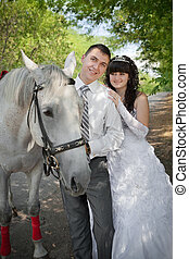 groom and the bride during walk in their wedding day against a grey horse