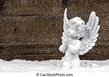 little white angel on wooden background in snow - little...