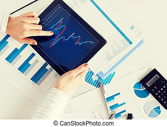 woman with tablet pc and chart papers