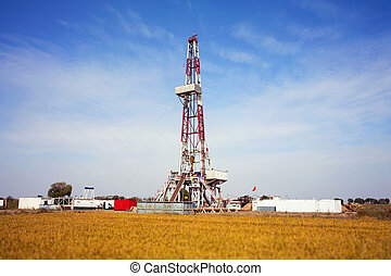 Drilling rig in autumn - Land drilling rig surround by rice...