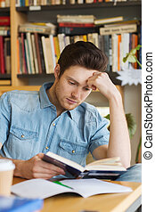 male student reading book in library - people, knowledge,...