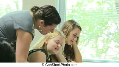 Teacher helping students with their - High school teacher...