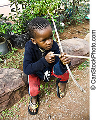 Poverty African child - Poor African child playing with some...