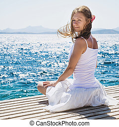 Woman sitting at the beach - Beautiful woman in white...
