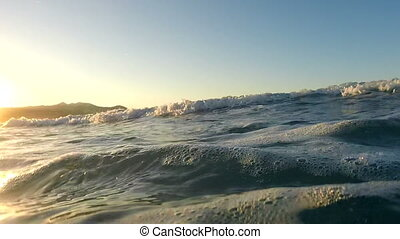 Waves on a beach at sunset - Waving water surface of the sea...