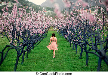 Woman enjoying spring in the green field with blooming trees...