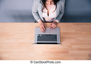 Top view portrait of a woman using laptop on the wooden desk...