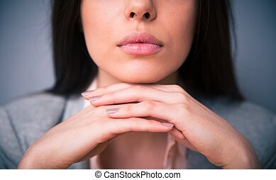 Closeup image of woman lips over gray