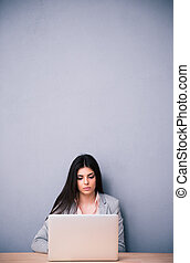 Young cute woman sitting at the table with laptop - Young...