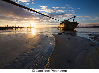 Old wrecked ship at sunrise in Kua