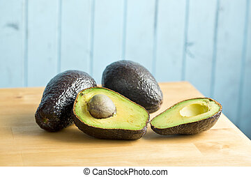 halved avocado on kitchen table - the halved avocado on...