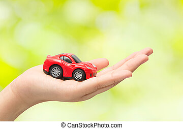 hand holding the model of car on green background. symbol...