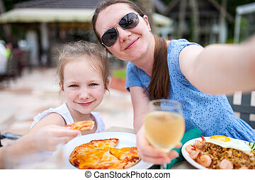 Mother and daughter at restaurant - Happy mother and her...