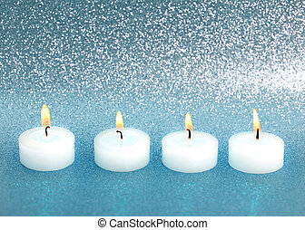 burning candles over silver blue shiny background - four...