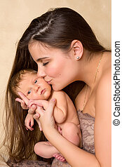 Mother kissing newborn baby - Beautiful young mother kissing...