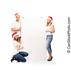 Three happy teenagers in Christmas hats holding a large...