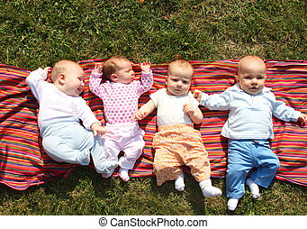 four babies - Four babies lying on colourful cloth in park