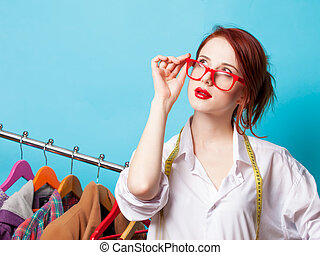 Young redhead designer with metric and clothes on blue...