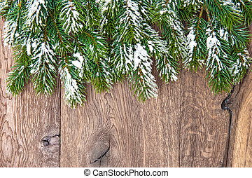 christmas tree branches over wooden background. green border...