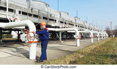 worker closes valve on installation for cooling gas at...