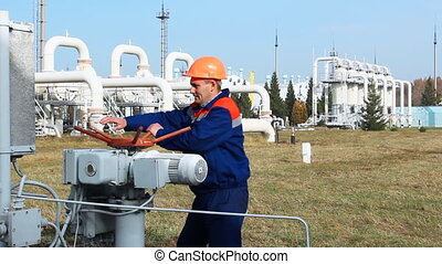 worker closes recirculation valve on compressor station of...