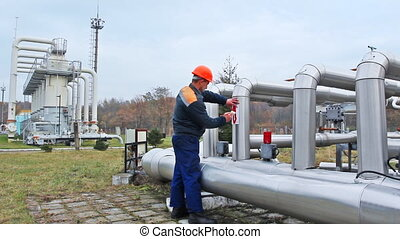 worker draws red arrows on pipes at compressor station of...