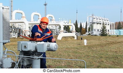 worker opens recirculation valve on compressor station of...