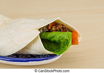 Burrito with salad, minced meat on the wood background