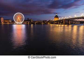 Nightly view of a spinning ferris wheel in Toulouse