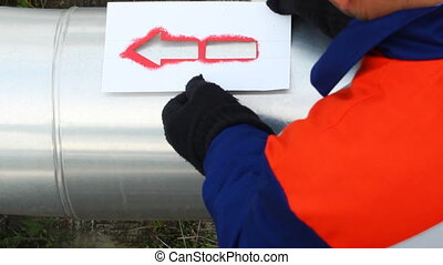 worker draws red arrow on pipes at compressor station of...