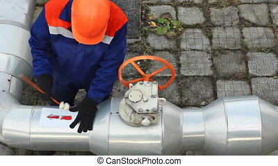 worker draws red arrow on pipes near valve at compressor...