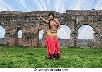 belly dancer with ancient Roman aqueducts ruins in the...