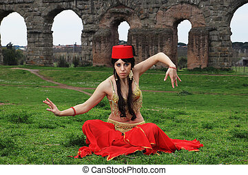oriental dancer - red hat belly dancer sitting in front of...