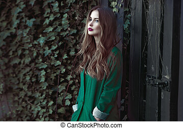 Fashion woman in green coat posing outdoors