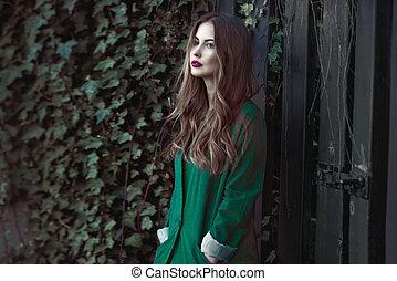 Fashion woman in green coat posing outdoors