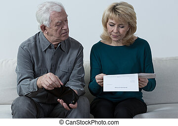 Aged couple analyzing unpaid bills - Aged couple sitting on...