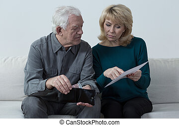 Counting money - Old couple analyzing home budget and...