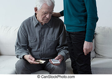 Poor senior man using calculator and counting money
