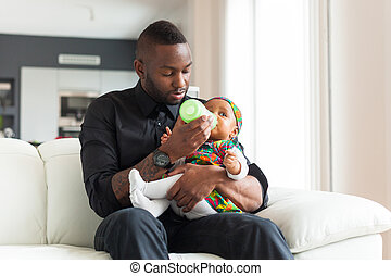 Young african american father giving milk to her baby girl...