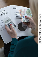 Analyzing family budget - Close-of poor woman analyzing...