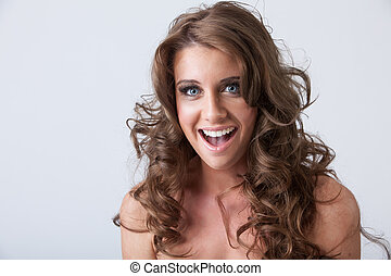 Surprised smiling young woman with healthy long curly hair