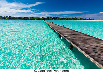 Wooden long jetty over lagoon in Maldives with amazing water...