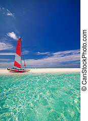 Sailing boat with red sail on beach of tropical island