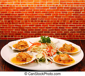 baked shellfish with a brick background on a wood table top