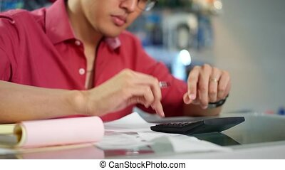 Chinese Man With Calculator Bills - Young asian entrepreneur...