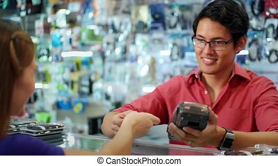 Customer Paying With Credit Card - Young asian entrepreneur...