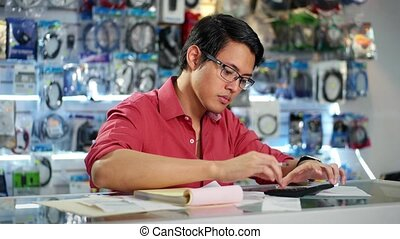 Man Working In Computer Shop - Young woman paying with...