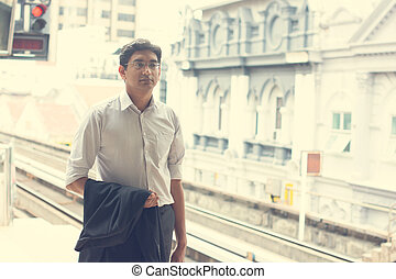 Candid Asian Indian businessman waiting at public train...